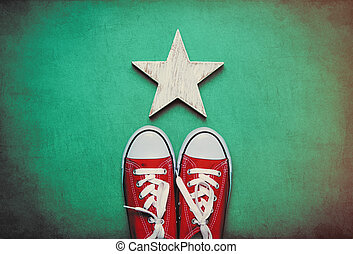 big red gumshoes and cute star shaped toy lying on the wonderful blue background