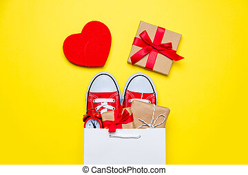 big red gumshoes, beautiful gifts and alarm clock in cool shopping bag and heart shaped toy on the wonderful yellow background