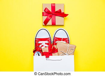 big red gumshoes, beautiful gifts and alarm clock in cool shopping bag on the wonderful yellow background