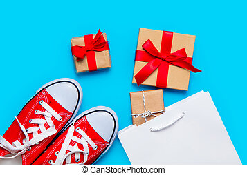 big red gumshoes, cool shopping bag and beautiful gifts on the wonderful blue background