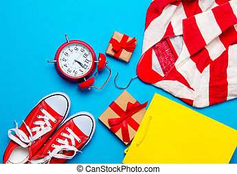 big red gumshoes, cool shopping bag, striped jacket on hanger, alarm clock and beautiful gifts on the wonderful blue background