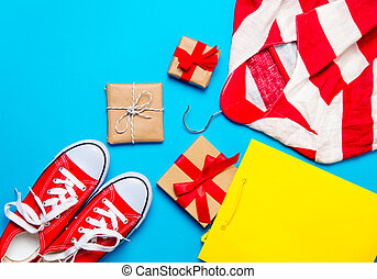 big red gumshoes, cool shopping bag, striped jacket on hanger and beautiful gifts on the wonderful blue background