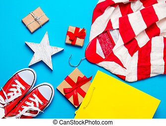 big red gumshoes, cool shopping bag, striped jacket on hanger, star shaped toy and beautiful gifts on the wonderful blue background