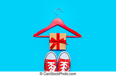big red gumshoes, hanger and beautiful gift on the wonderful blue background