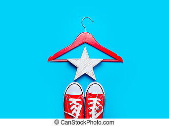 big red gumshoes, hanger and beautiful star shaped toy on the wonderful blue background