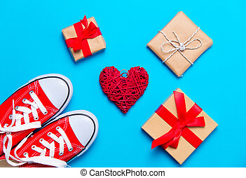 big red gumshoes, heart shaped toy and beautiful gifts on the wonderful blue background
