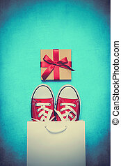 big red gumshoes in cool shopping bag and beautiful gift on the wonderful blue background