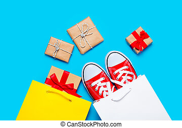big red gumshoes in cool shopping bag and beautiful gifts near other shopping bag on the wonderful blue background