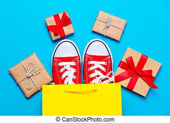big red gumshoes in cool shopping bag and beautiful gifts on the wonderful blue background