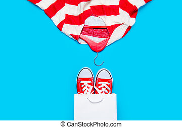 big red gumshoes in cool shopping bag and stried jacket on hanger on the wonderful blue background
