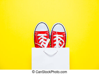 big red gumshoes in cool shopping bag on the wonderful yellow background
