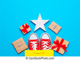 big red gumshoes in cool shopping bag, star shaped toy and beautiful gifts on the wonderful blue background