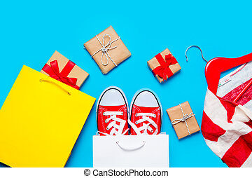 big red gumshoes in cool shopping bag, striped jacket on hanger and beautiful gifts near other shopping bag on the wonderful blue background