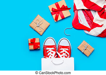 big red gumshoes in cool shopping bag, striped jacket on hanger and beautiful gifts on the wonderful blue background