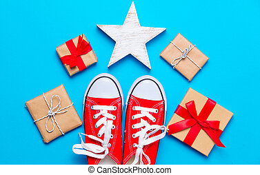 big red gumshoes, star shaped toy and beautiful gifts on the wonderful blue background