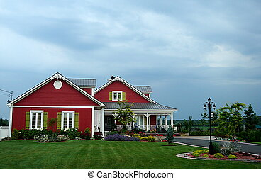 Big red house and cropped lawn with cloudy sky