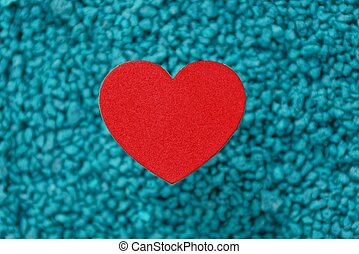 red paper heart on a blue background