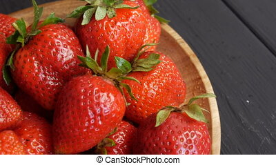 Big red ripe strawberry with green leaves on a bamboo eco ...
