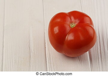Big red tomato on the table. Close up. White background