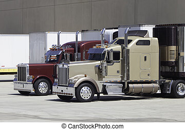 Two big rig trucks waiting at the warehouse dock to be unloaded and loaded with cargo.