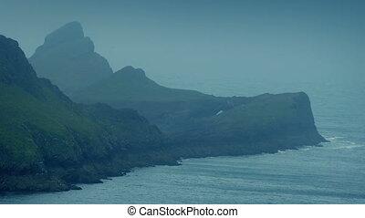 Big Rocky Cliffs By The Ocean - Rocky cliffs by sea on misty...