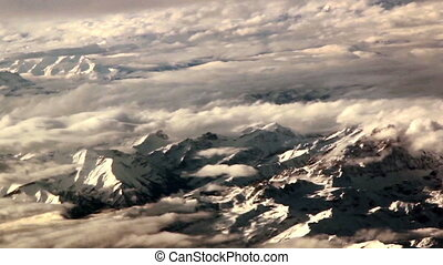 Big rocky mountains covered with snow thin clouds and the white mountain