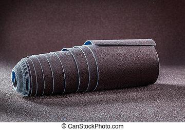 big roll of sandpaper on brown abrasive background