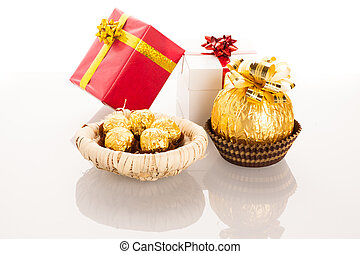 Big round chocolate candy wrapped in golden foil with big bow on top and small candy in basket like babies next to mother.
