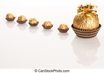 Big round chocolate candy wrapped in golden foil with big bow on top and small candy standing in line like babies behind mother.