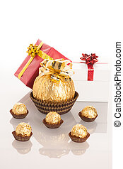 Big round chocolate candy wrapped in golden foil with big bow on top and small candy standing in line like babies around mother.