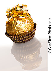 Big round chocolate candy wrapped in golden foil with big bow on top.