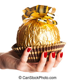 Big round chocolate candy wrapped in golden foil with big bow on top lying in palm with red nails.