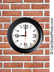 Big round clock on red brick wall closeup