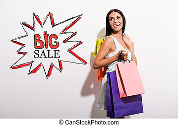 Big sale! Happy young woman in dress carrying colorful...
