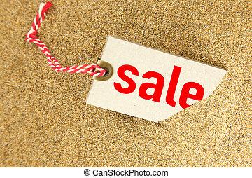 Big sale tag on sand closeup