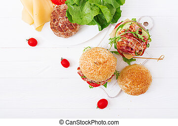 Big sandwich - hamburger burger with beef, cheese, tomato, cucumber and fried bacon. Flat lay. Top view