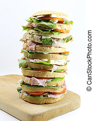 big sandwich with cheese ham tomato on a cutting board and white