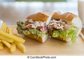 big sandwich with ham, cheese, vegetables and French fries