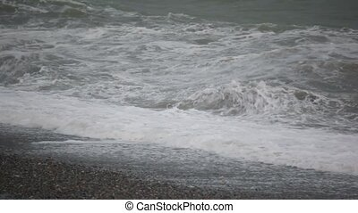 big sea surf waves in storm on pebble coast, dull weather