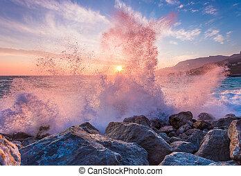 Big sea wave breaks against a stone at sunrise