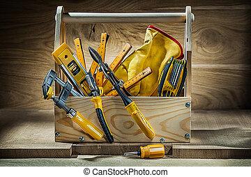 big set of working tools in vintage wooden toolbox on wood background