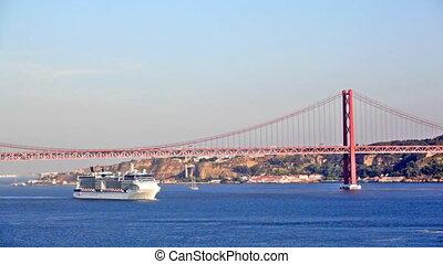 big ship floats under the bridge on April 25 in Lisbon, Portugal