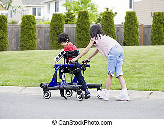 Big sister helping younger disabled brother in walker - Big...