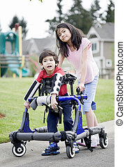 Big sister helping younger disabled brother to walk in his walker outside