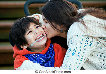 Big sister kissing disabled little brother seated in wheelchair