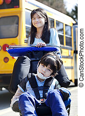 Big sister pushing disabled brother in wheelchair at school