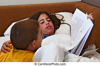 Big sister reading a bedtime book for her little brother - siblings sharing quality time before bed