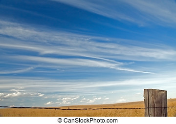 Big sky - Stratus clouds over farmers field with barbed wire...