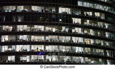 big skyscraper at night in city with shone windows and...