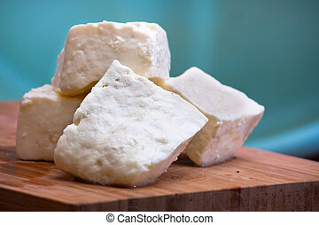Big slices of Curd cheese on cutting board.
